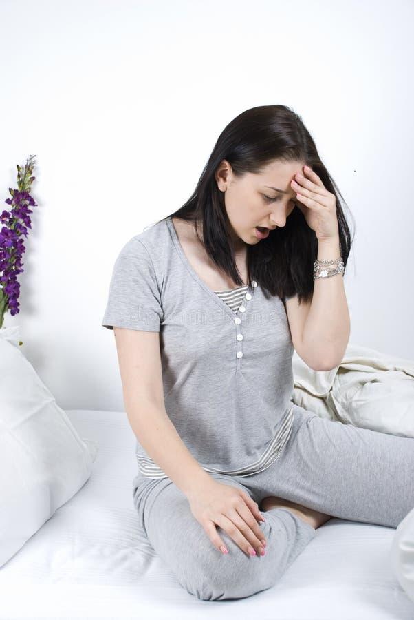 Mulher com dor principal na cama fotografia de stock