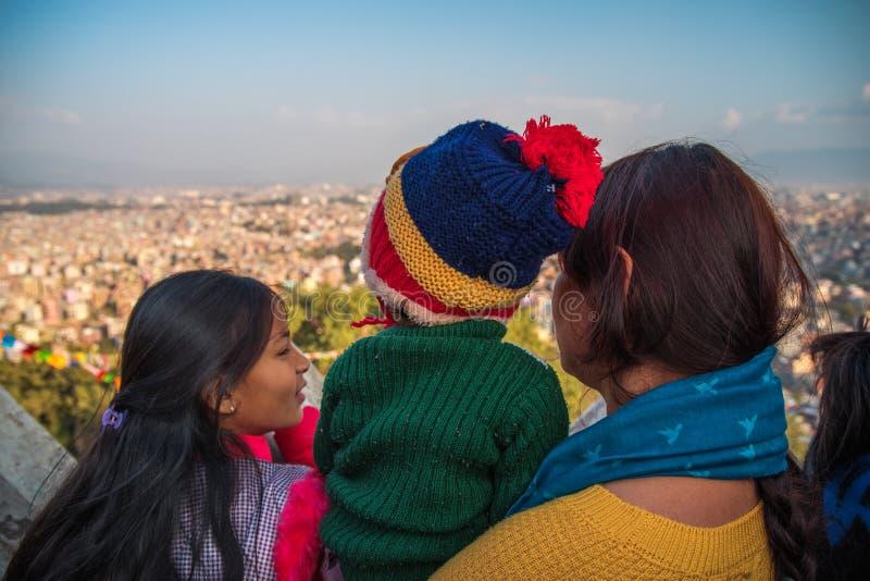 A mulher com duas crianças olha o Kathmandu Valley fotografia de stock