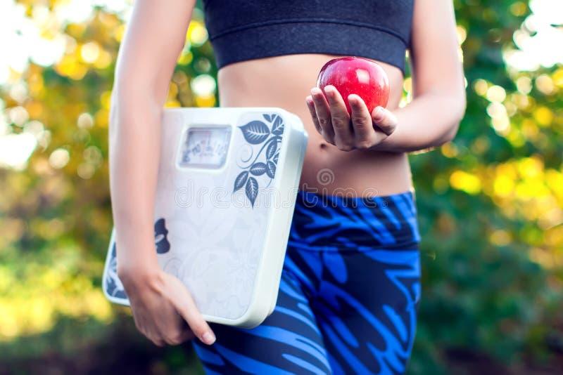 Mulher com a escala e a maçã vermelha exteriores Emagrecimento, dieta e healt fotografia de stock royalty free