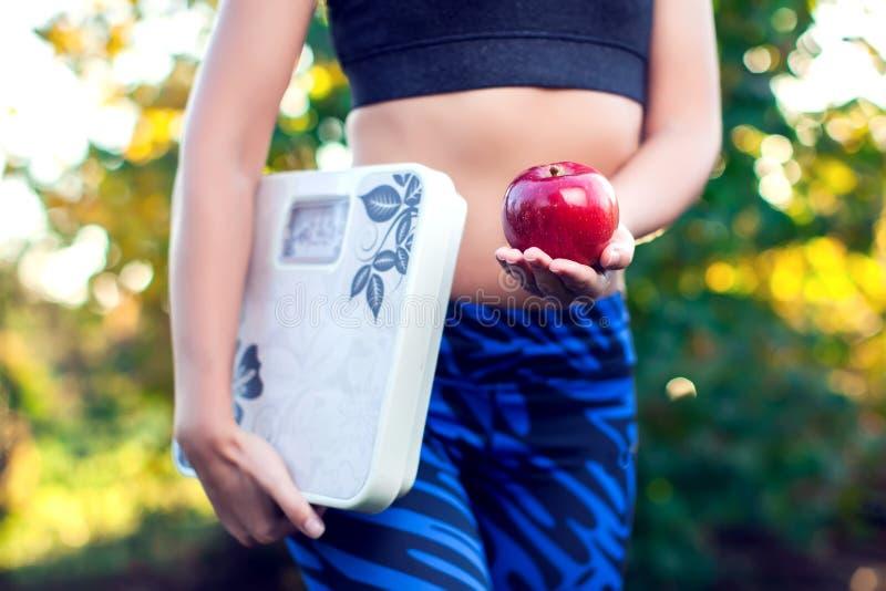 Mulher com a escala e a maçã vermelha exteriores Emagrecimento, dieta e healt imagens de stock royalty free
