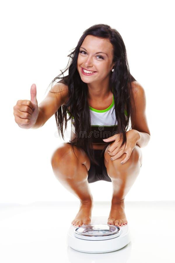 Mulher com escalas após uma dieta bem sucedida fotos de stock