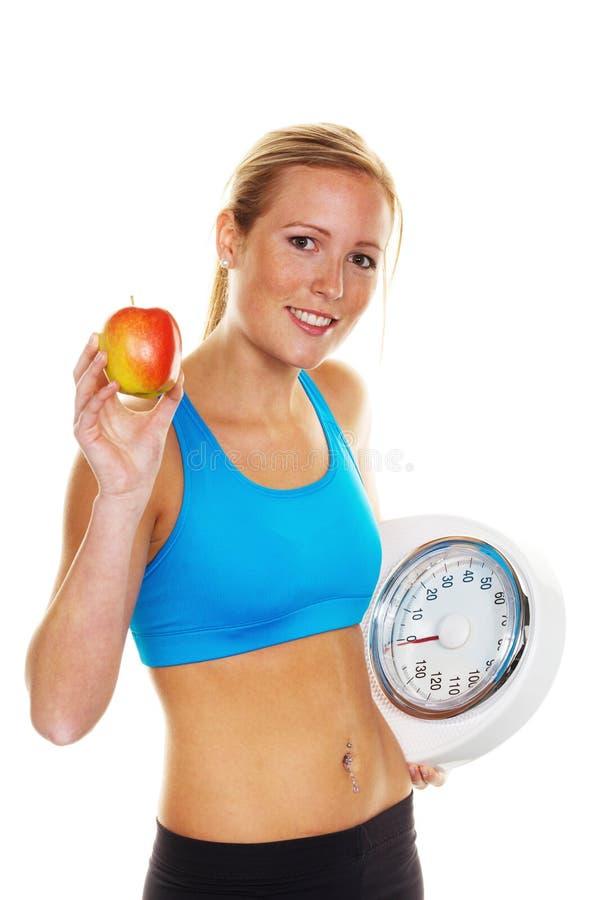Mulher com escalas e maçã imagem de stock royalty free