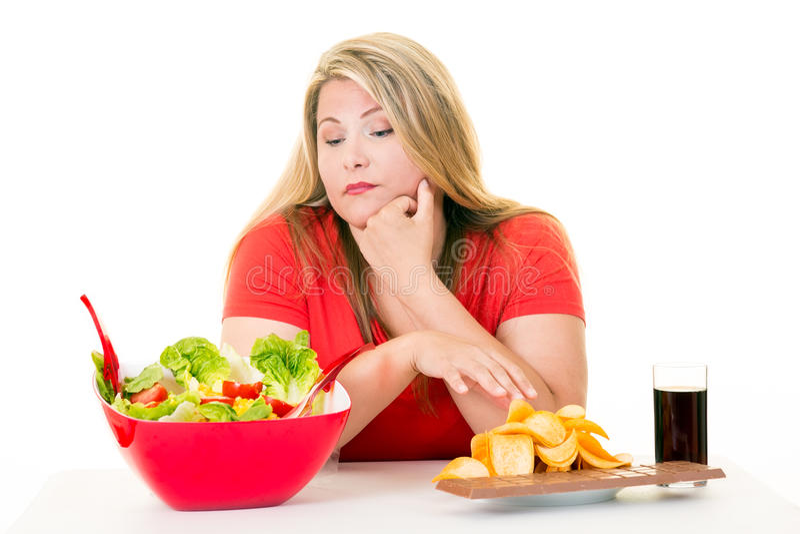 Mulher com escolha da bacia e da comida lixo de salada imagem de stock royalty free