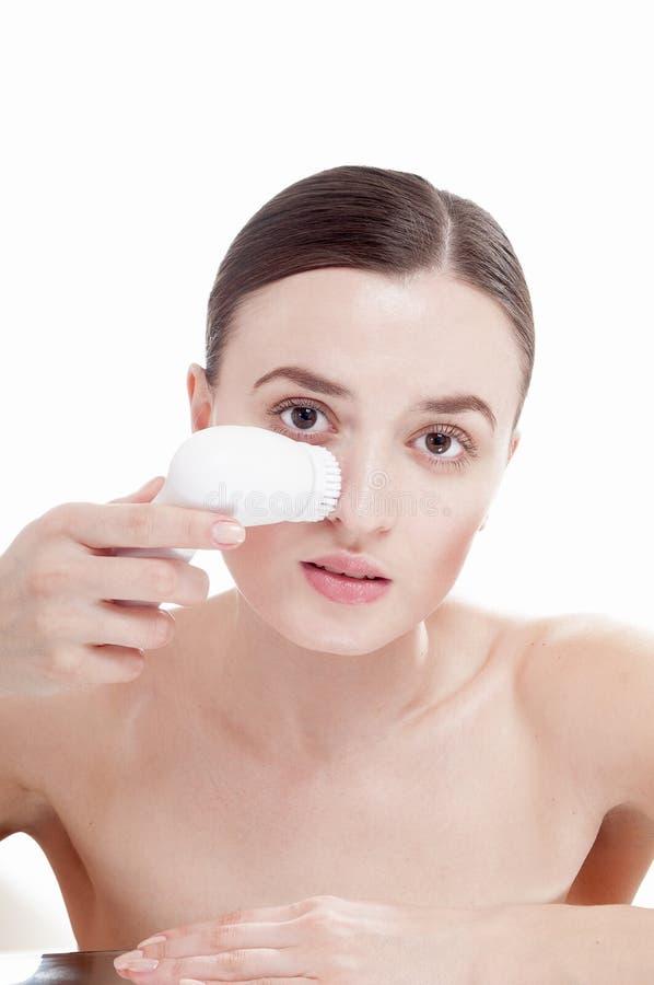 Mulher com a escova para o facial profundamente de limpeza. foto de stock