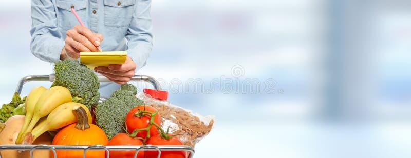 Mulher com escrita do carrinho de compras no bloco de notas foto de stock