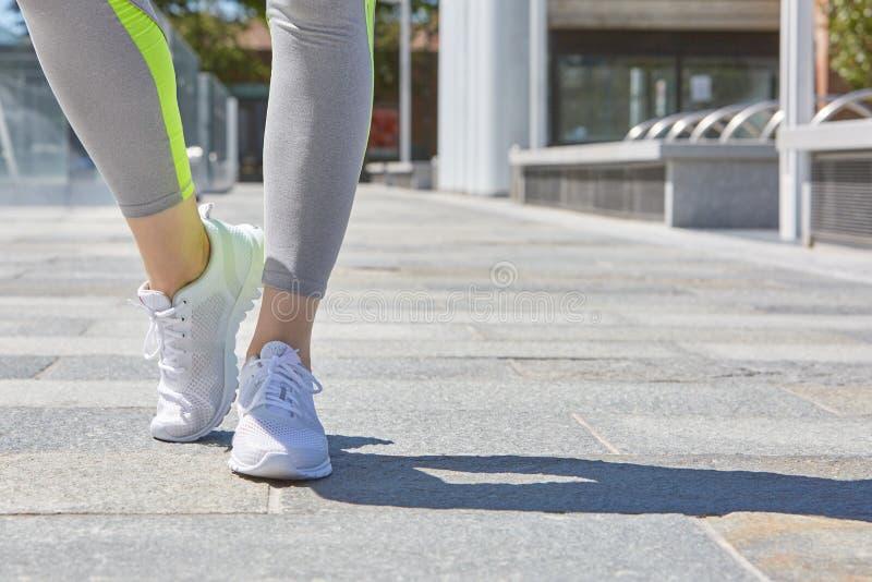 A mulher com esporte branco calça exterior pronto para ser executado fotografia de stock