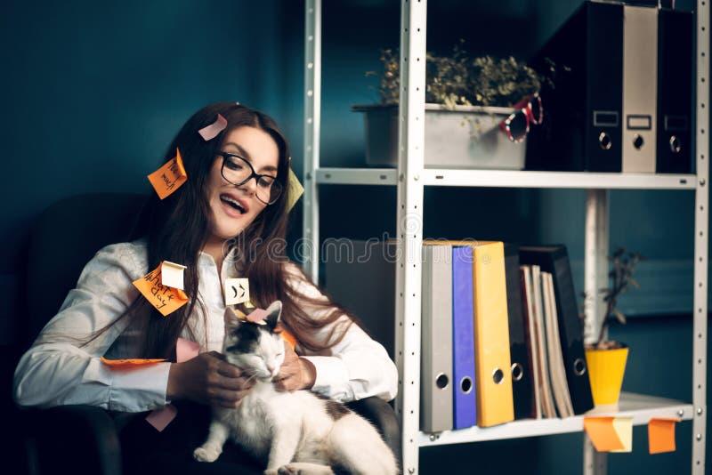 Mulher com etiquetas por todo o lado em seu gato guardando fotos de stock royalty free