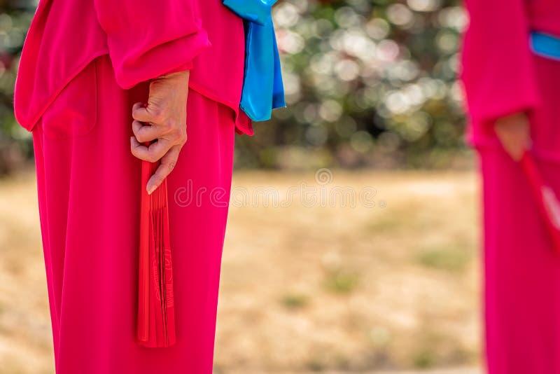 Mulher com fã vermelho Tai Chi de execução fotos de stock