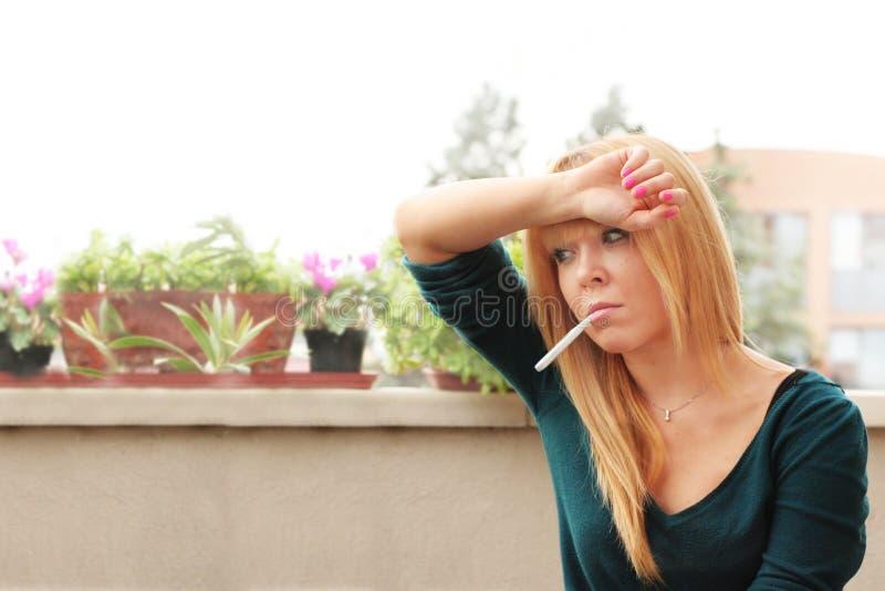 Mulher com febre e dor de cabeça fotografia de stock royalty free