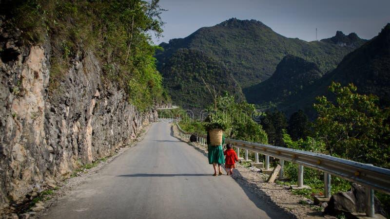 Mulher com a filha na roupa vietnamiana tradicional com uma cesta atrás de sua parte traseira que anda na estrada imagem de stock