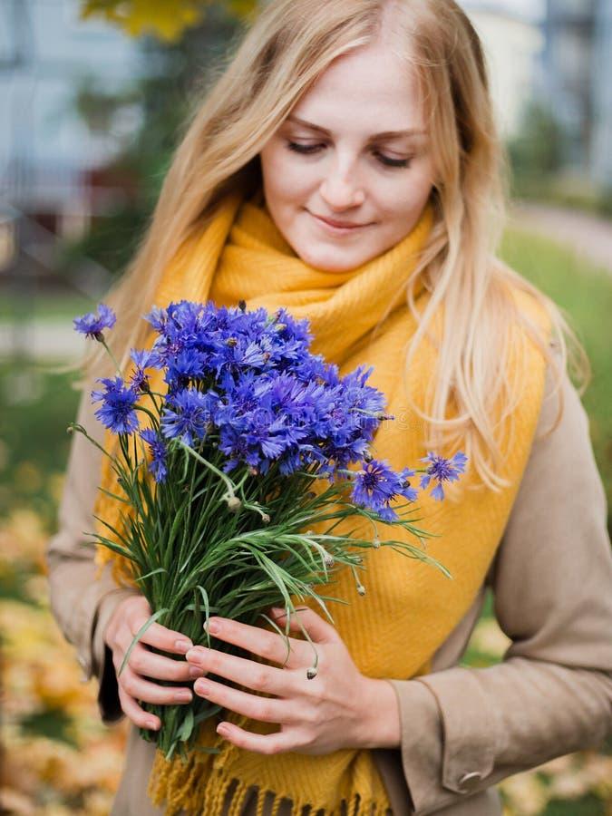 Mulher com flores, ramalhete da centáurea na mão fêmea imagens de stock