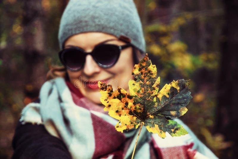 Mulher com a folha de bordo colorida na natureza do outono, filtro retro foto de stock