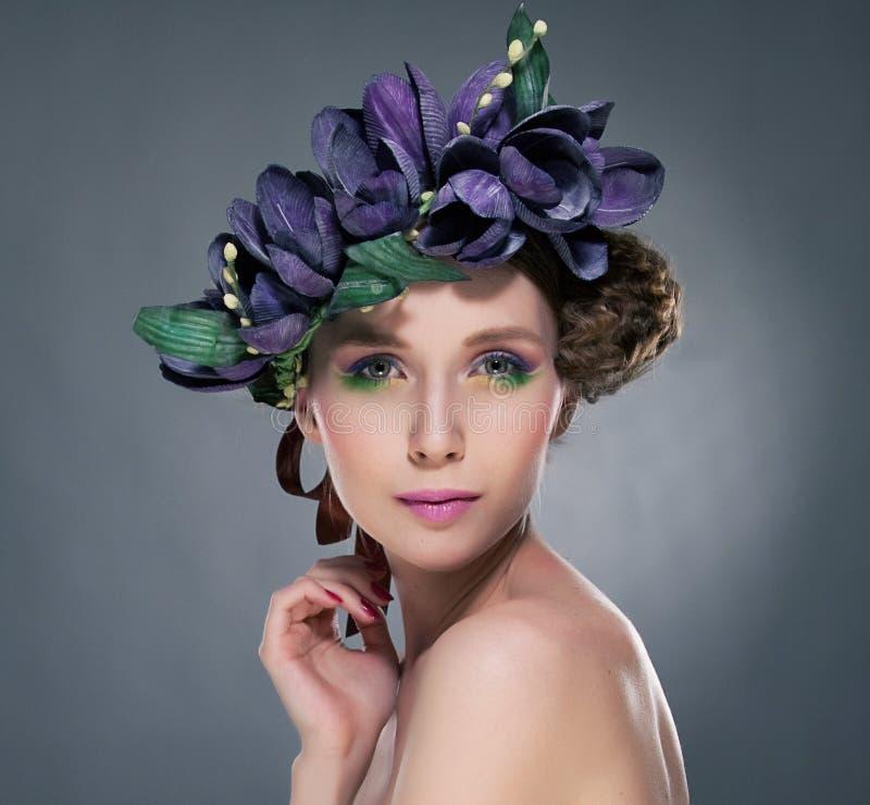 Carisma. Brunette brilhante refinado com folhas e flores. Romance fotografia de stock royalty free