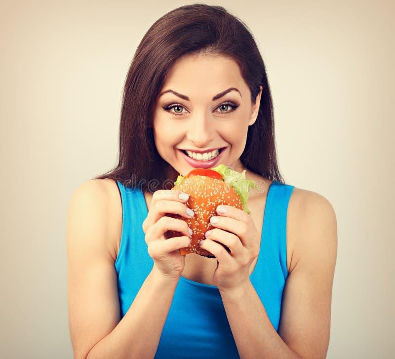 Mulher com fome feliz entusiasmado que quer morder o hamburguer saboroso no fundo azul closeup imagem de stock