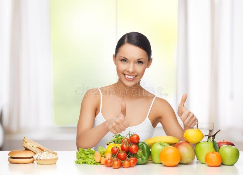 Mulher com frutos que rejeita a comida lixo fotografia de stock royalty free