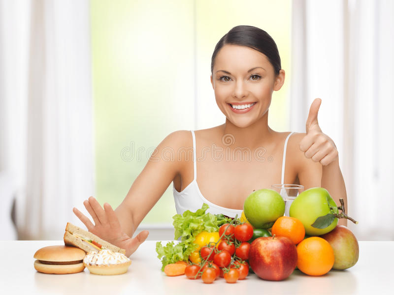 Mulher com frutos que rejeita a comida lixo fotos de stock