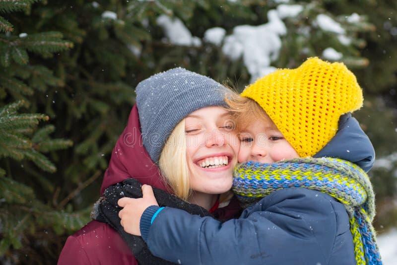 Mulher com fundo nevado de sorriso da natureza do inverno do filho Natal e ano novo Lenço morno do chapéu da mamã e da criança bo imagens de stock