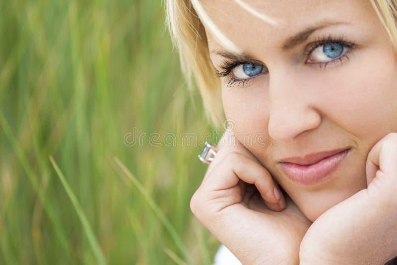 Mulher com fundo verde dos olhos azuis do cabelo louro fotografia de stock royalty free