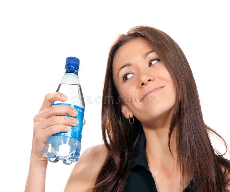 Mulher com a garrafa ainda da água potável pura que guarda à disposição imagens de stock royalty free