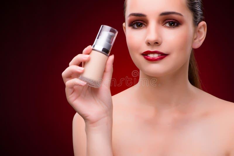 A mulher com a garrafa do creme do skincare foto de stock