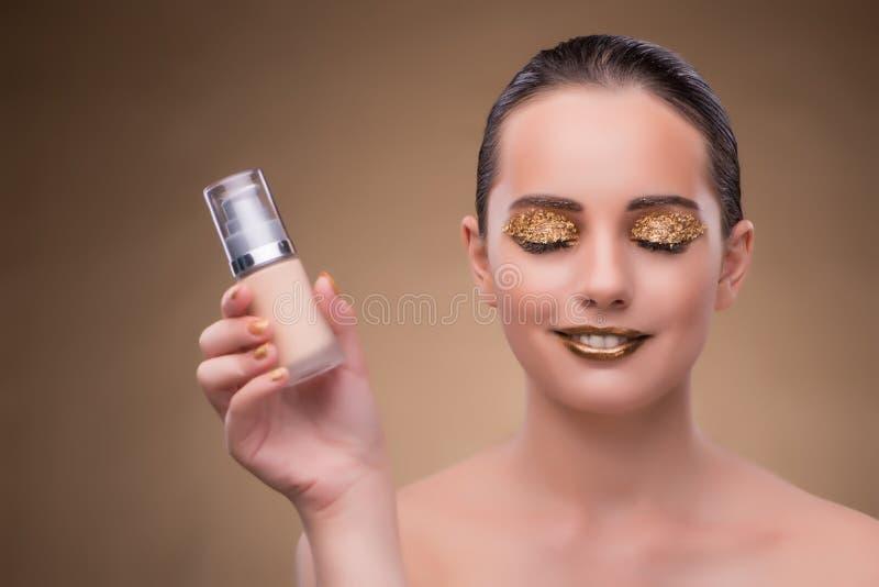 A mulher com a garrafa do creme do skincare imagem de stock