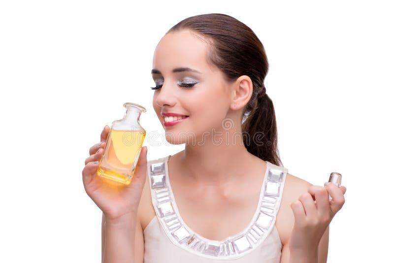 A mulher com a garrafa do perfume isolada no branco imagem de stock
