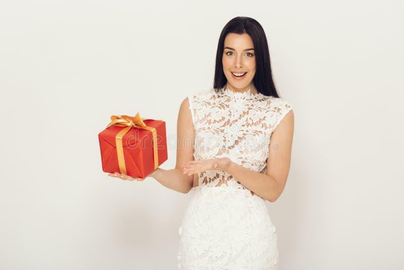 Mulher com giftbox no vestido branco sobre o fundo claro Menina bonita com caixa foto de stock royalty free