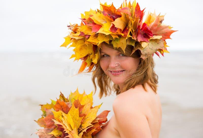 Mulher com a grinalda da folha de bordo no outono fotografia de stock