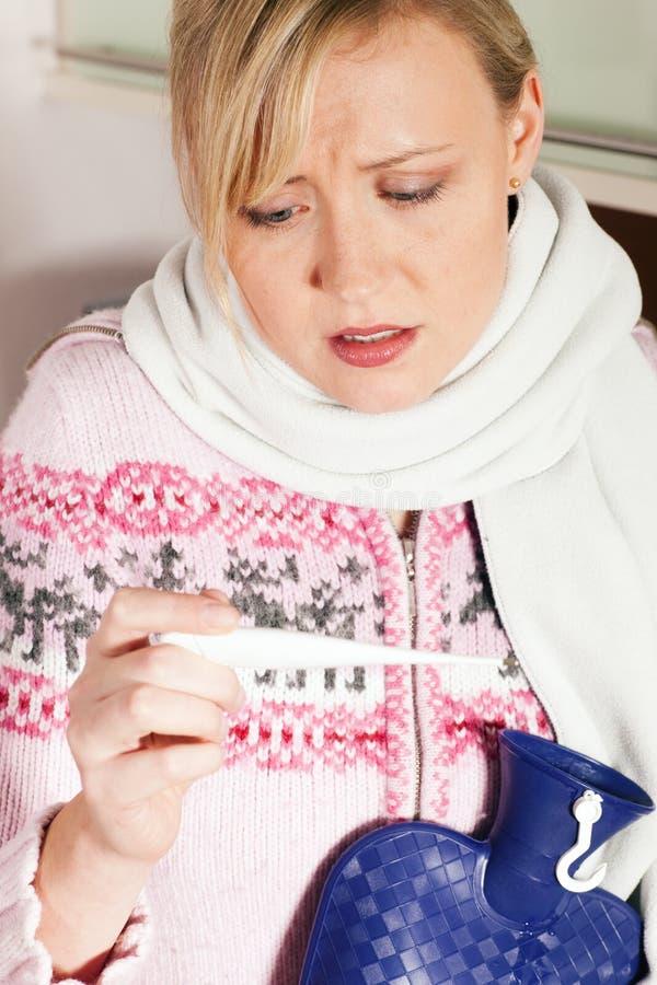 Mulher com a gripe que toma sua temperatura imagens de stock royalty free
