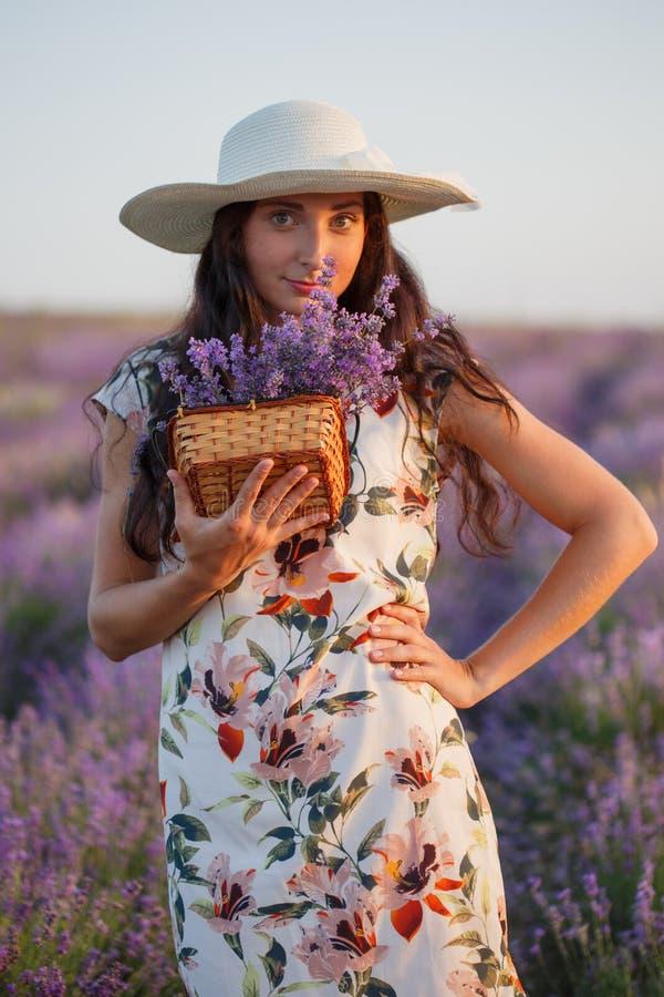 Mulher com grupo da alfazema na cesta de vime fotografia de stock