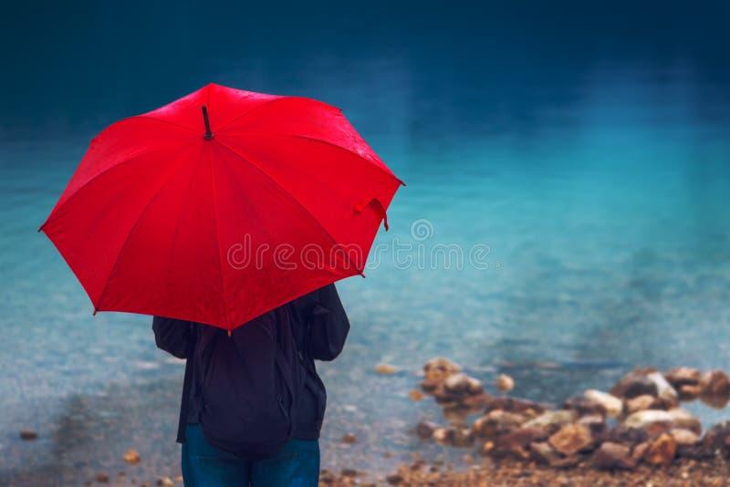A mulher com guarda-chuva vermelho contempla na chuva imagens de stock