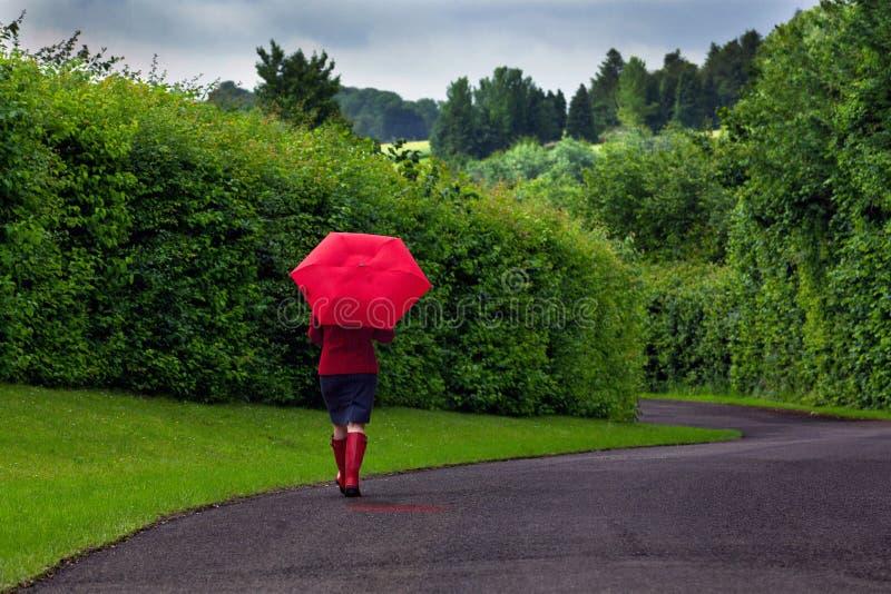 Mulher com guarda-chuva vermelho em um dia nublado. imagem de stock royalty free