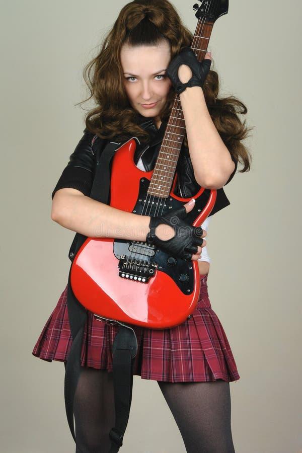 Mulher com guitarra vermelha imagem de stock royalty free