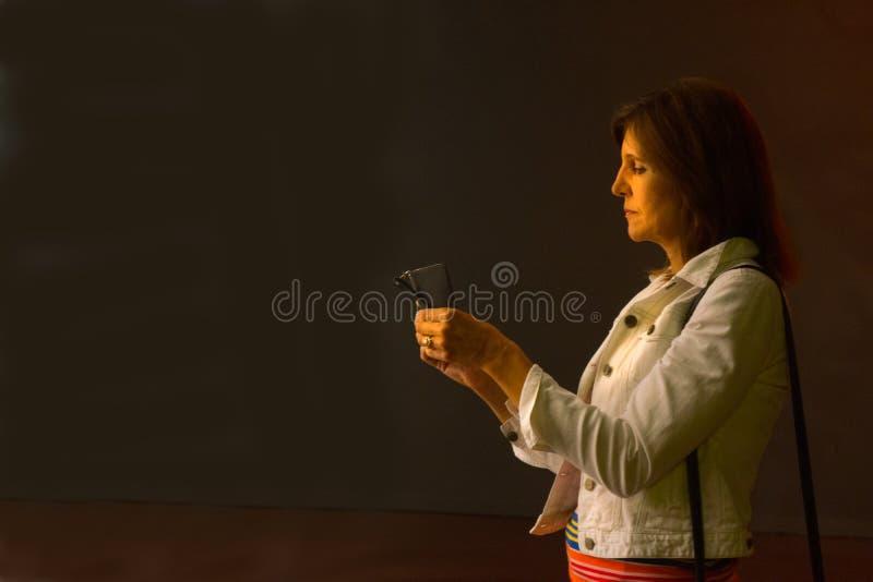 Mulher com iluminação indireta do telefone celular fotos de stock