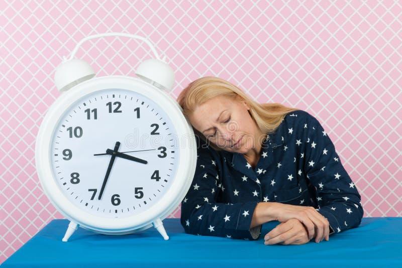Mulher com insônia e o despertador grande foto de stock