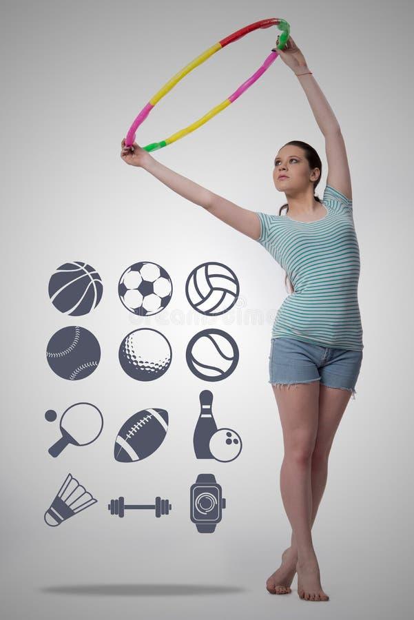 A mulher com laço do hula no conceito do esporte imagem de stock