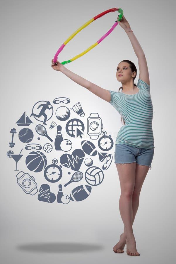 A mulher com laço do hula no conceito do esporte foto de stock