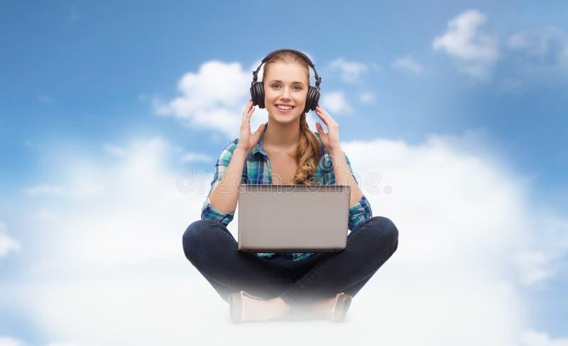 Mulher com laptop e fones de ouvido fotos de stock