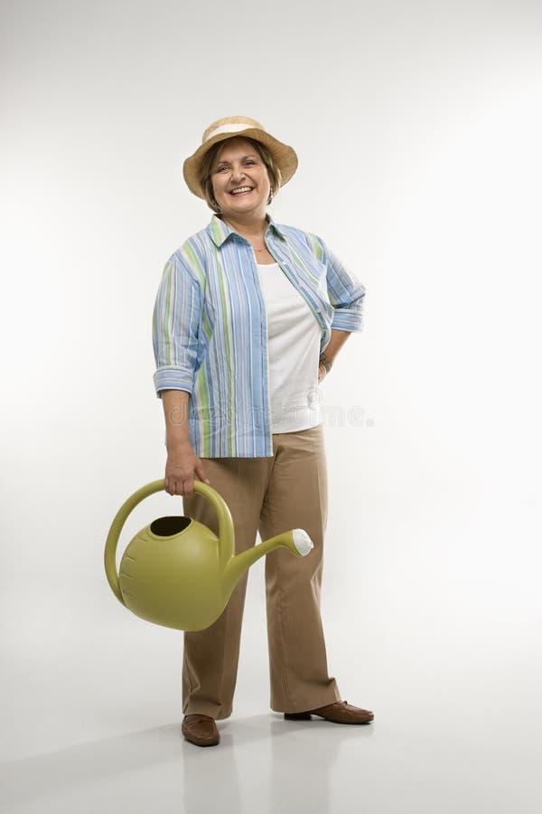 Mulher com lata molhando. foto de stock