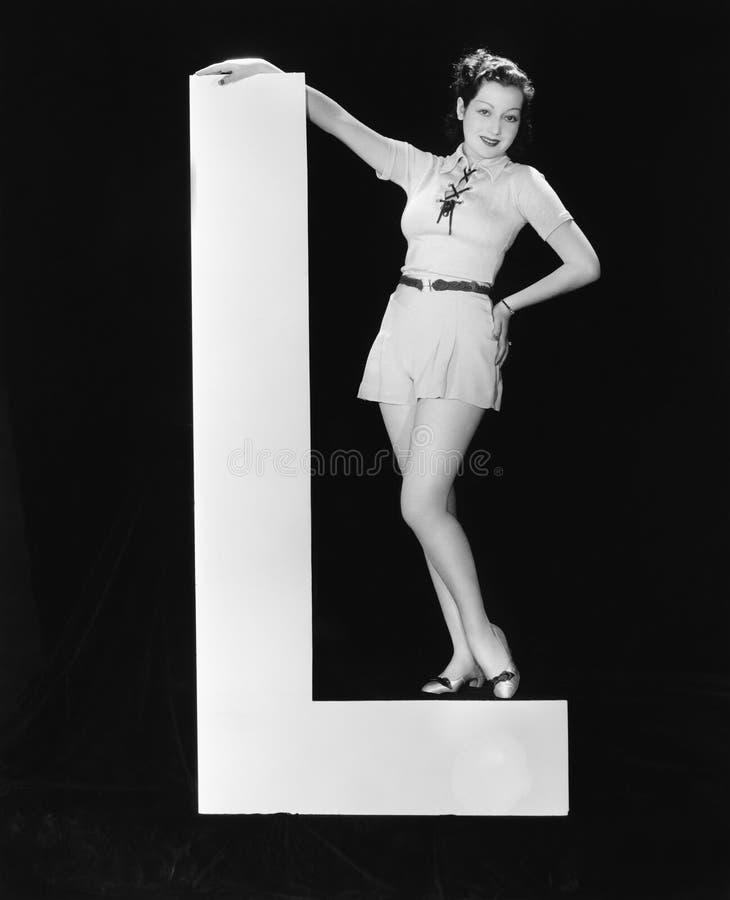 Mulher com letra enorme L (todas as pessoas descritas não são umas vivas mais longo e nenhuma propriedade existe Garantias do for imagens de stock
