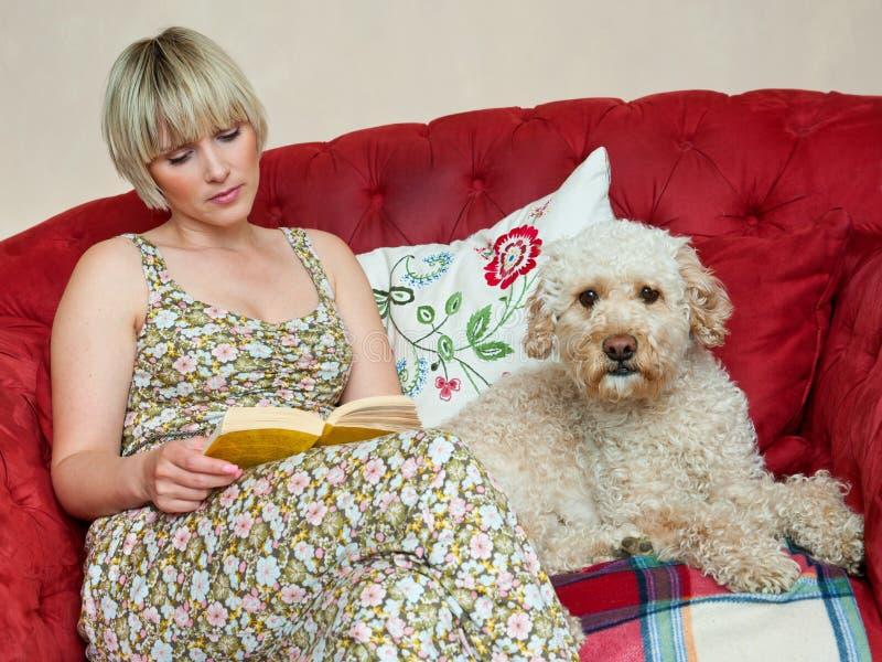 Mulher com livro e cão imagem de stock royalty free