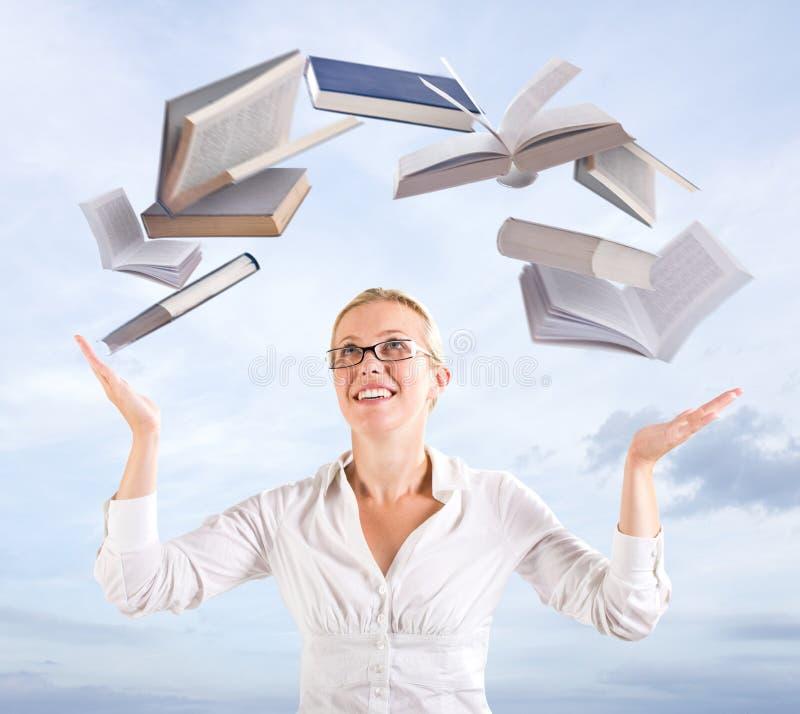 Mulher com livros de vôo fotografia de stock royalty free