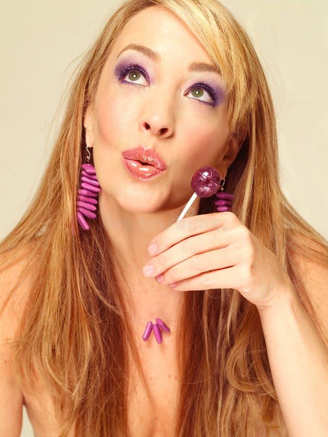 Mulher com lollipop roxo imagem de stock