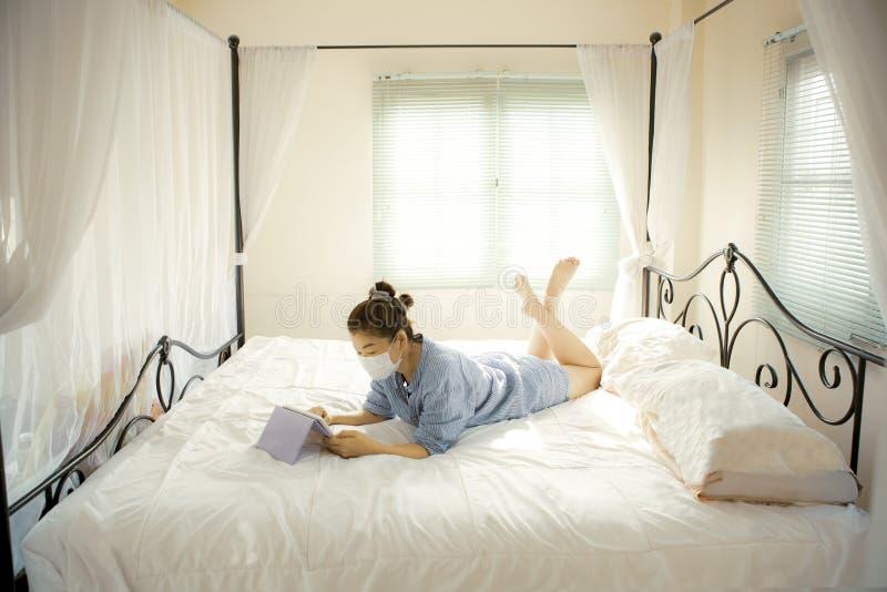Mulher com máscara de proteção na mão deitada no sofá-cama na sala de estar em casa conversando com um dispositivo de internet imagens de stock