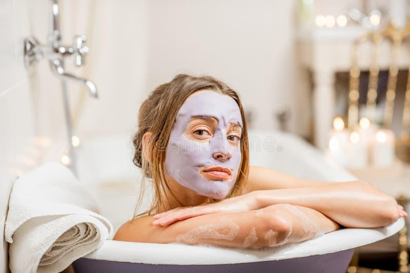 Mulher com máscara facial no banheiro fotos de stock