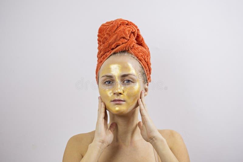 Mulher com máscara protetora higiênica dourada levantar fotos de stock