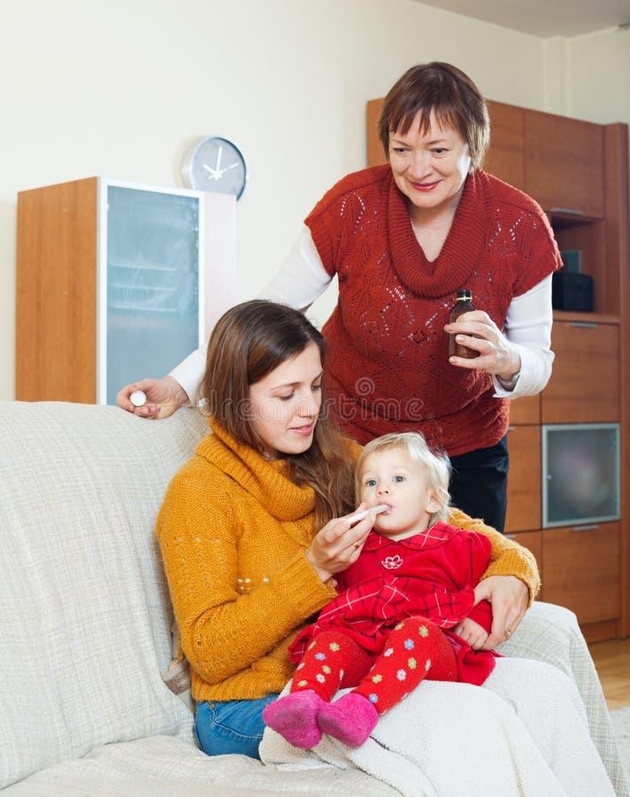Mulher com a mãe madura que dá o medicamento ao bebê imagens de stock