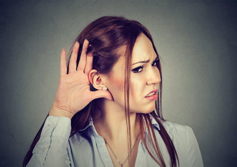 Mulher com mão ao gesto da orelha que escuta com cuidado fotos de stock royalty free