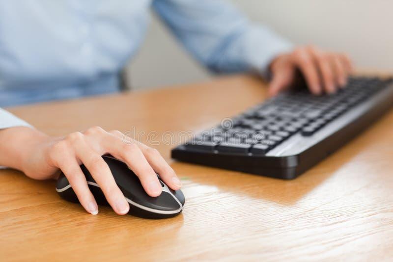 Mulher com mãos no rato e no teclado fotos de stock