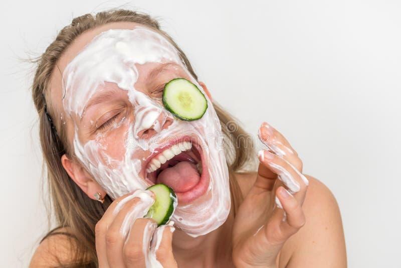 Mulher com m?scara de creme natural e pepinos em sua cara fotos de stock